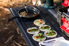 Breakfast Omlette Wraps on Car Tailgate. Cooking breakfast omlettes on car tailgate during camping trip Stock Photos