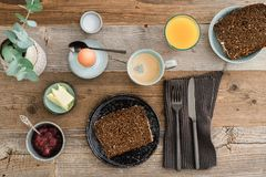 Breakfast for one. Breakfast table shot from above with bread, egg, coffee, orange juice and jam Royalty Free Stock Photos