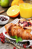 Breakfast with orange juice and fresh croissant. Breakfast with orange juice, fresh croissant and cake on wooden table Stock Photos