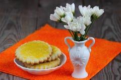 Breakfast on orange serviete. Baked cookie  and flowers on orange serviete Royalty Free Stock Images
