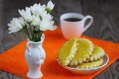 Breakfast on orange serviete. Baked cookie with tea and flowers on orange serviete Shallow DOF stock image