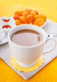 Breakfast in orange tones. White cup of coffee with breakfast items on the orange textured linen napkin Royalty Free Stock Image