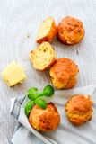 Yellow Cheese and cheese   muffins. Breakfast  from   organic  bio  yellow cheese, home made cheese   muffins  and fresh basil   on a  white wooden background Royalty Free Stock Photos