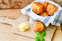 Yellow Cheese and cheese   muffins. Breakfast  from   organic  bio  yellow cheese, home made cheese   muffins  and fresh basil   on a  white wooden background Royalty Free Stock Image
