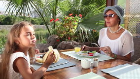 Breakfast at outdoor cafe. Mother and adorable little girl having breakfast at outdoor cafe stock footage