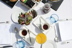 Hotel breakfast outodoor in a sunny day. Breakfast outside in the hotel on a sunny morning. Cup of fresh strawberries, typical cream breakfast cakes, different royalty free stock photo