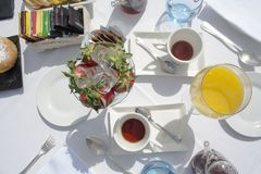 Hotel breakfast outodoor in a sunny day. Breakfast outside in the hotel on a sunny morning. Cup of fresh strawberries, typical cream breakfast cakes, different stock photography