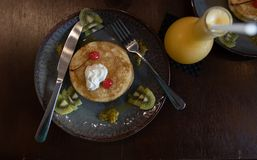 Breakfast with pan cakes. And Two glass of orange juices in flask shapes glass on a wooden table stock photo