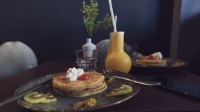 Breakfast with pan cakes. And Two glass of orange juices in flask shapes glass on a wooden table royalty free stock photo