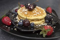 Breakfast with pancake and berries. Pancake for breakfast served in black plate with cranberries, cherries and strawberries Stock Images