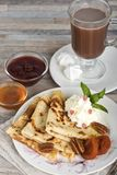 Breakfast. Pancakes, honey, strawberry jam, cream, dried apricots, nuts and hot chocolate or cocoa or coffee stock photo