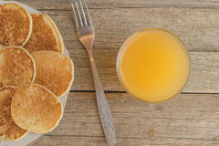 Breakfast with pancakes and orange juice with metal fork on a wooden table Royalty Free Stock Images