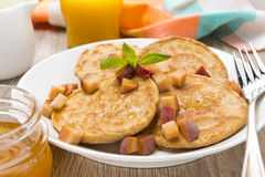 Breakfast with pancakes, peaches and honey, close-up Royalty Free Stock Images