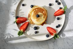 Breakfast, pancakes with strawberries, blueberries and maple syrup. Sweet breakfast royalty free stock photography