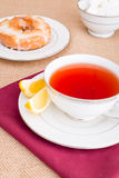 Breakfast with pastries, and hot tea with lemon. Stock Photography
