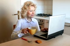 Breakfast & pc. A senior woman with a cup of tea and notebook Royalty Free Stock Image