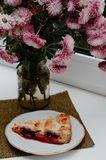 Breakfast. A piece of a pie with fruit on a white plate and fresh flowers. Stock Photography