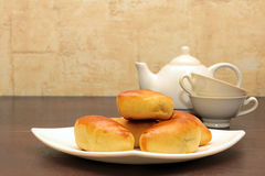 Breakfast with pies. Patty on a plate against the background of the teapot and cups Stock Image