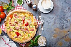 Breakfast pizza with scrambled egg, ham and tomatoes royalty free stock image