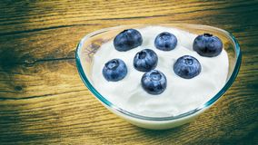 Fresh blueberries in low fat yogurt on a wooden background Stock Images