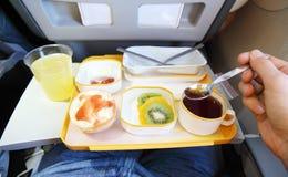 Breakfast in plane. (fruit, small bun, juice and tea). Passenger tries tea by teaspoon royalty free stock image