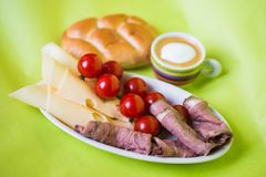 Breakfast plate with cherry tomatoes, cheese, roastbeef, bun and cup of coffee Stock Photo