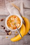 Breakfast, corn flakes with a spoon, raisins, bananas with a sprig of wheat on burlap. royalty free stock photo