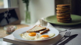 Breakfast plate. Fried eggs with bread toasts and pancake stack on kitchen table stock footage