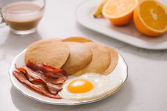 Breakfast plate with pancakes, eggs, bacon and fruit. Stock Photo