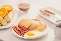 Breakfast plate with pancakes, eggs, bacon and fruit. Stock Photography