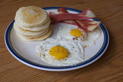 Breakfast  Plate. A breakfast plate of two peppered eggs sunny side up, a stack of silver dollar pancakes and vegetarian bacon strips Stock Photo