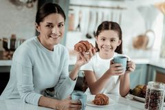 Pleasant woman having breakfast with a daughter royalty free stock images