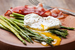 Breakfast: poached egg, baked asparagus Royalty Free Stock Photo