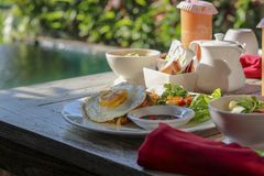 Breakfast by the pool in tropical resort in Bali. Exotic summer royalty free stock image