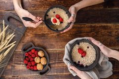 Breakfast from porridge with blueberries and fresh raspberries. Still life on a wooden background with hands. View from above Royalty Free Stock Photo
