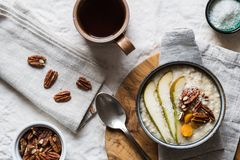 Breakfast porridge bowl with fruit nuts and tea royalty free stock photos