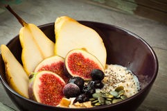 Breakfast porridge. Healthy breakfast porridge of oats topped with fresh sliced pear, sliced fig, blueberries, coconut, chia and pumpkin seeds Stock Photography