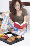 Breakfast reading on bed Royalty Free Stock Photo