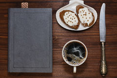 Breakfast while reading the book. Light breakfast of sandwiches with spreading cheese and coffee and old book with bookmark on the wooden table royalty free stock image