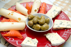 Breakfast. On a red plate in the center on a little plate of olives, lies around the cheese, red fish, blue cheese, picture up close Stock Photos
