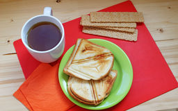 Breakfast on a red and wooden background. Crispbread, sandwiches and cup of hot tea on the table - tasty meal Royalty Free Stock Images