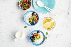 Breakfast, rice porridge or natural yoghurt with assorted berries, fruits and nuts: kiwi, pomegranate, blueberries. Almonds, dried apricots in small bowls on a stock photo