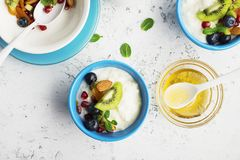 Breakfast, rice porridge or natural yoghurt with assorted berries, fruits and nuts: kiwi, pomegranate, blueberries. Almonds, dried apricots in small bowls on a stock photos