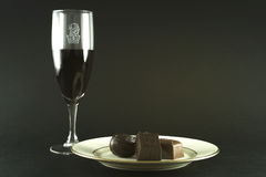Breakfast of the Rich and Famous. A plate of Belgian chocolate and a fine glass of very dark wine. Isolated on matte black background Royalty Free Stock Image