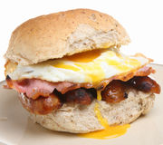 Breakfast Roll with Sausage, Bacon & Egg. Wholewheat roll with bacon, sausages and fried egg Stock Images