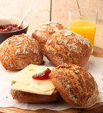 Breakfast with rolls. Breakfast with bread rolls, cheese, marmalade and orange juice at plank background Royalty Free Stock Photo