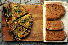 Breakfast with rustic frittata and bread on a wooden board Stock Images