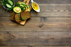 Breakfast for safety weight loss. Avocado toast with rye bread, lime, olive oil and greens on dark wooden background top. View Stock Images
