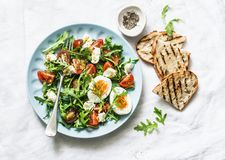 Breakfast salad - arugula, cherry tomatoes, mozzarella and boiled egg with olive oil, mustard, lemon dressing on a light backgroun royalty free stock photography