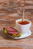 Breakfast with salami sandwich and cup of tea Stock Photo